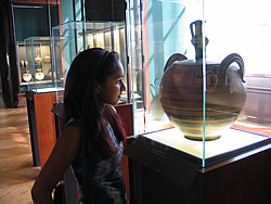 Romina admires a vase at the Louvre